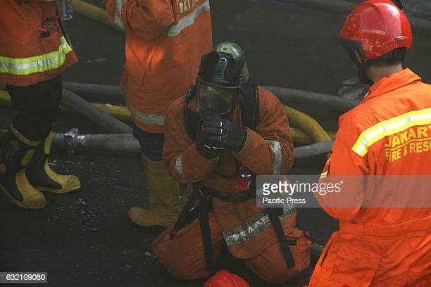 Firefighters wearing gas mask when trying to extinguish a fire that burns shopping center Pasar Senen Jakarta The fire was reported at 445 am and has...
