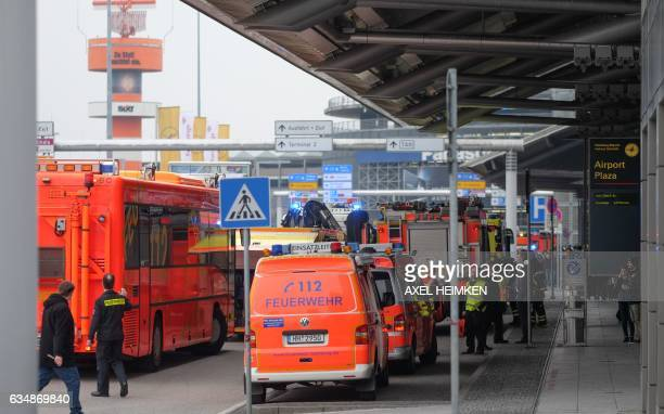 Firefighters with multiple vehicles stand in front of Hamburg airport as passengers leave the terminal on February 12 2017 in Hamburg northern...