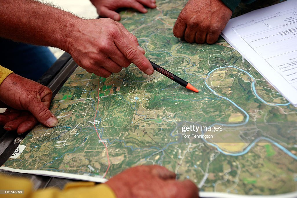 Firefighters with the Lone Camp volunteer fire department map out their strategy for cutting fire lines on the 101 Ranch on April 20, 2011 in Palo Pinto, Texas. The area wildfires had calmed due to cooler tempratures, higher humidity, and calm winds overnight.