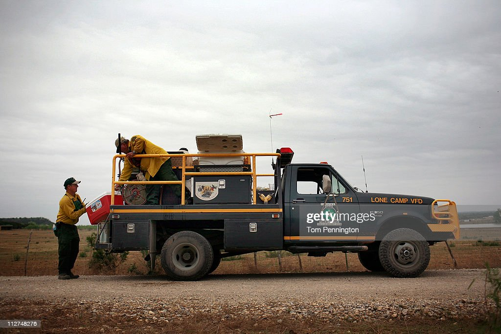 Firefighters with the Lone Camp volunteer fire department take a break from cutting fire lines on the 101 Ranch on April 20, 2011 in Palo Pinto, Texas. The area wildfires had calmed due to cooler tempratures, higher humidity, and calm winds overnight.