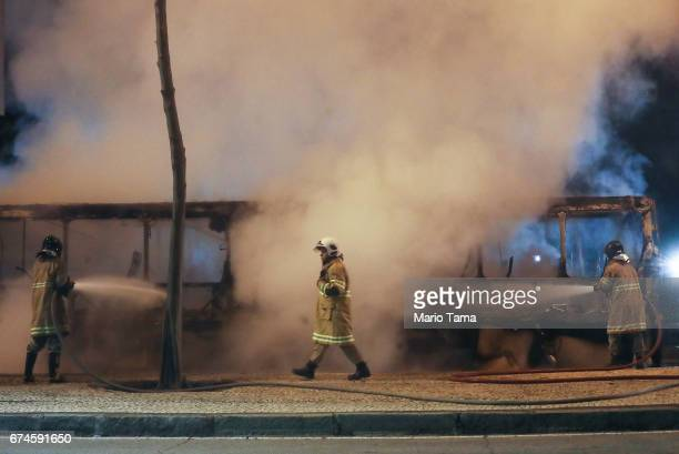 Firefighters work as a bus burns after being set on fire by protestors during a nationwide general strike on April 28 2017 in Rio de Janeiro Brazil...