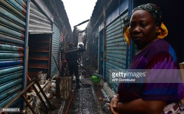 Firefighters work as a woman looks on amid debris in the market after a fire devastated the building during the night on September 18 2017 in Abobo...
