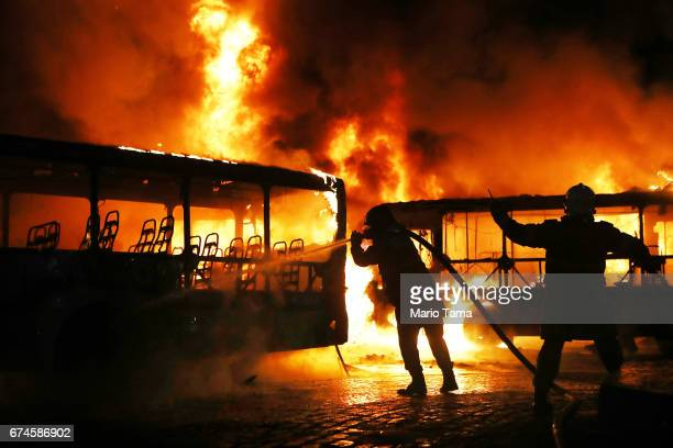 Firefighters work as buses burn after being set on fire by protestors during a nationwide general strike on April 28 2017 in Rio de Janeiro Brazil...