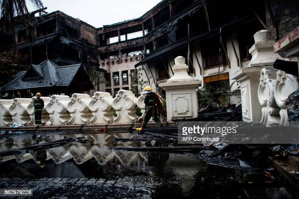Firefighters work at the scene after a fire at Kandawgyi Palace hotel in Yangon on October 19 2017 One person died in a predawn blaze on October 19...
