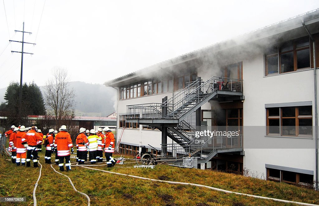 Firefighters work at the scene of a fire at a house with a workshop for handicapped people in Titisee- Neustadt, southern Germany on November 26, 2012. Fourteen people died after a fire broke out. AFP PHOTO / Martin Ganz GERMANY OUT