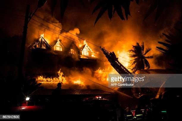 Firefighters work at the scene of a fire at Kandawgyi Palace hotel in Yangon early on October 19 2017 One person died in a predawn blaze on October...