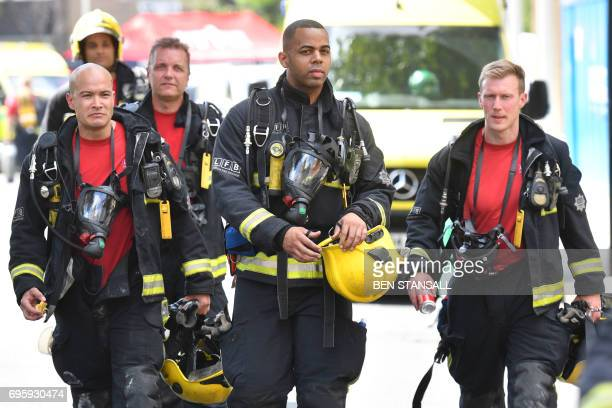Firefighters work at the scene where a fire ripped through Grenfell Tower a residential block in west London on June 14 2017 At least six people were...