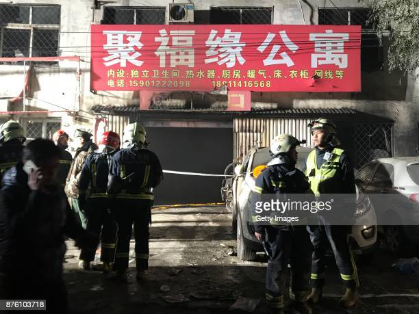 Firefighters work at the site after a house fire at Daxing District on November 19 2017 in Beijing China Nineteen people were killed and eight others...