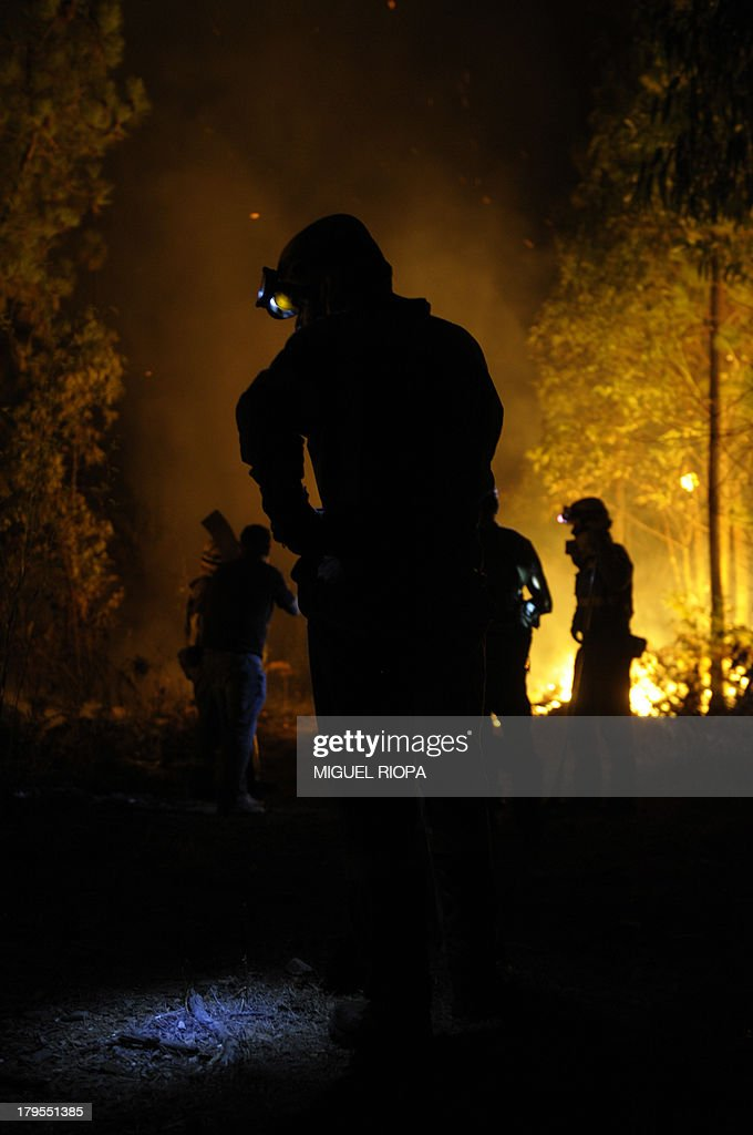 Firefighters work at the site of a wildfire in the village of Barbudo, some 40 km from Vigo, northwestern Spain, in the early hours of September 5, 2013. AFP PHOTO/ MIGUEL RIOPA