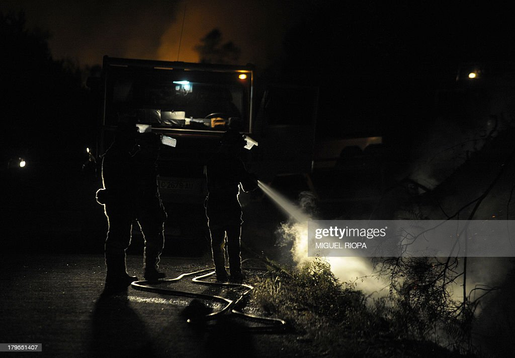 Firefighters work at the site of a wildfire in the village of Barbudo, some 40 km from Vigo, northwestern Spain, in the early hours of September 5, 2013.