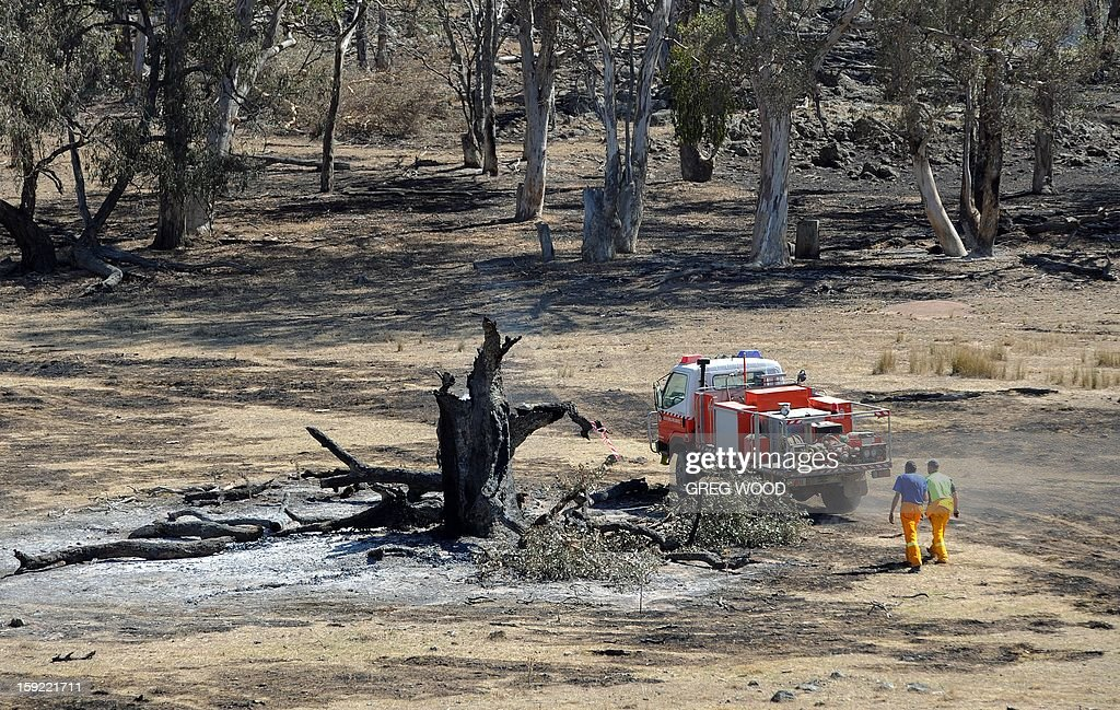 Firefighters work in a paddock blackened by recent bushfires near Bookham, a small village in the Yass Shire in the southern region of Australia's New South Wales state, on January 10, 2013. Fires have been raging across Australia for nearly a week and while many have been contained, 126 are still burning and at least 15 remain out of control in the country's most populous state, New South Wales. AFP PHOTO / Greg WOOD