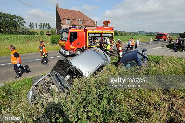 Firefighters work near two damaged cars along a road on June 30 2013 in Godewaersvelde northern France following a traffic accident between two...