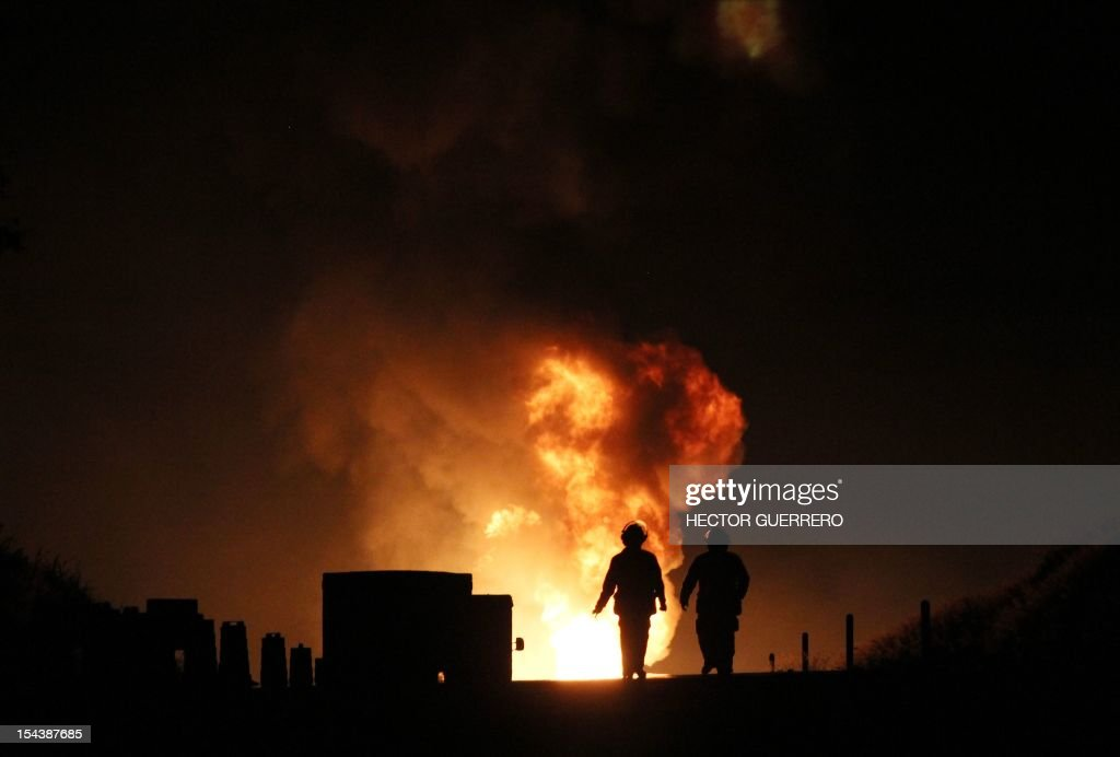 Firefighters work next to flames caused by the explosion of a gas pipeline in Zapotlanejo, 30 km from Guadalajara city, Jalisco State, Mexico on October 19, 2012. The explosion injured two people and forced the evacuation of 600 residents, according to local authorities. AFP PHOTO/Hector Guerrero