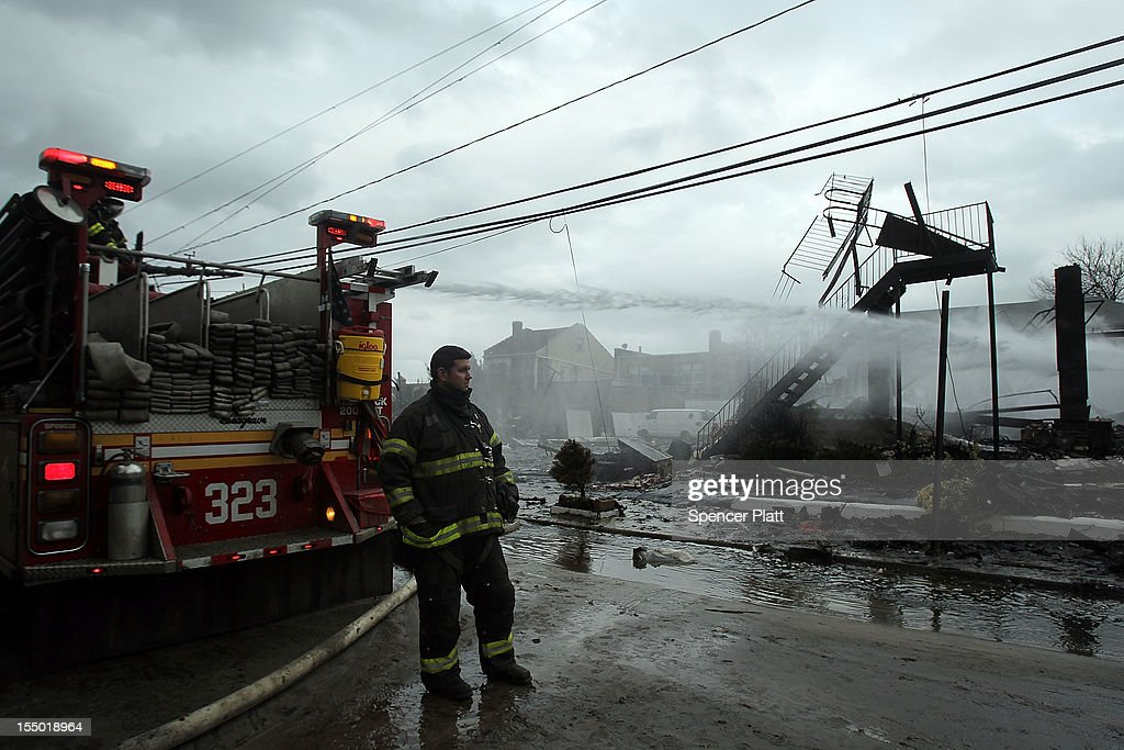 Firefighters work on a fire at a building after Hurricane Sandy on October 30, 2012 in the Rockaway section of the Queens borough of New York City. At least 40 people were reportedly killed in the U.S. by Sandy as millions of people in the eastern United States have awoken to widespread power outages, flooded homes and downed trees. New York City was hit especially hard with wide spread power outages and significant flooding in parts of the city.