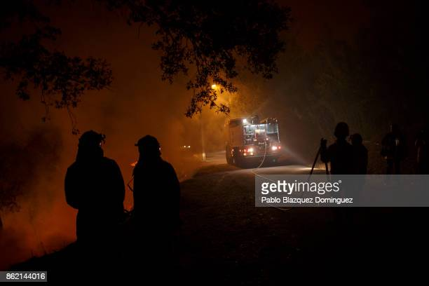 Firefighters work on a forest wildfire next to Vilarinho village near Lousa on October 16 2017 in Coimbra region Portugal At least 36 people have...