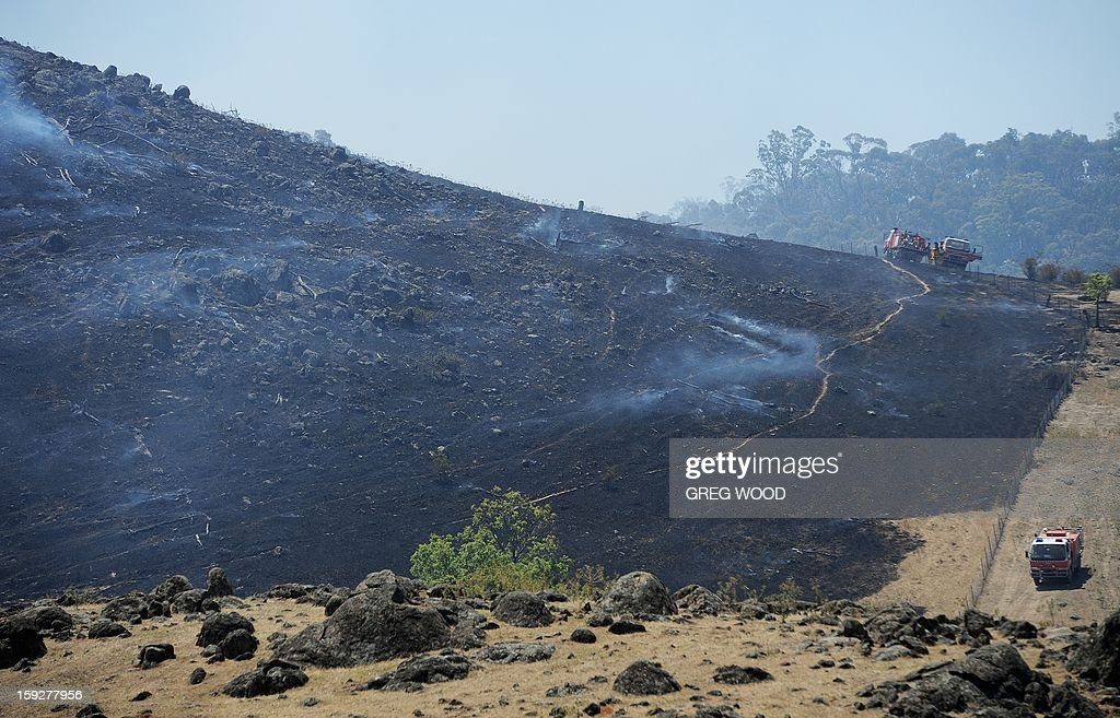 Firefighters (R) work on a scrubfire as it burns up a hillside south of Bookham, near Yass in the southern region of Australia's New South Wales state, on January 11, 2013. After two days of cooler weather, heat and high winds returned to much of the country as fire crews tackled the infernos that have been burning for a week, 18 of them out of control in the most populous state of New South Wales. AFP PHOTO / Greg WOOD