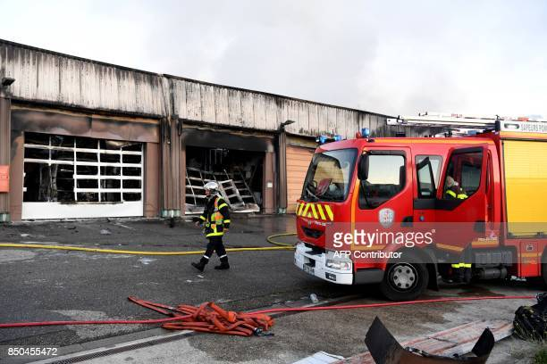 Firefighters work on September 21 2017 in Grenoble eastern France near a burntout garage which contained about fifty vehicles of the French...
