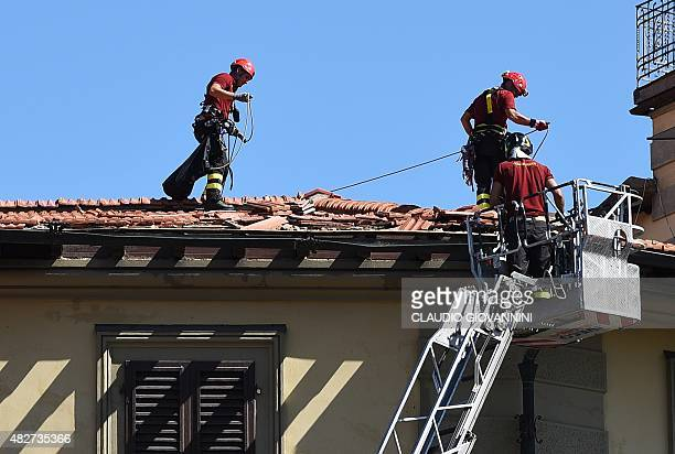 Firefighters work on the roof of a house damaged by tornado in downtown Florence on August 2 2015 Some twenty people were wounded on August 1 when a...