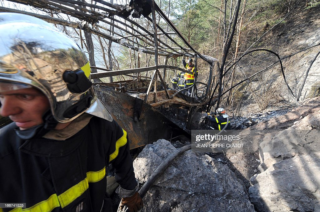 Firefighters work on the wreckage of a bus transporting British citizens that crashed on April 16, 2013 near Bourg d'Oisans as they were leaving the French Alps resort of l'Alpe d'Huez. The accident killed at least one person, severely wounded three others, and slightly injured 21. In total, 53 people were aboard the bus, including two drivers.