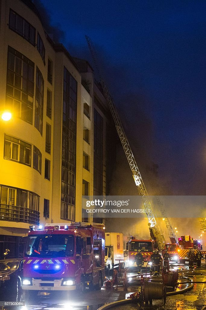 Firefighters work to contain a fire in a building on rue de Charonne in Paris on May 2, 2016. 180 firefighters were deployed to contain the fire in the six-storey building in which textiles and furniture are stored, according to the fire brigade. Two people, including one firefighter, were injured in the blaze. / AFP / GEOFFROY