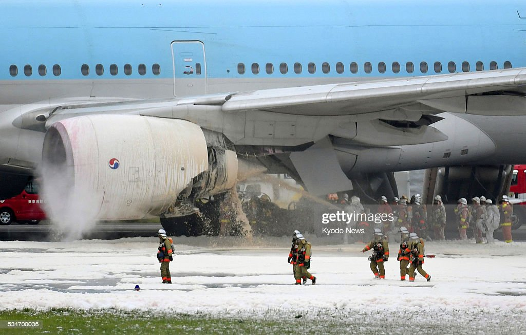 Firefighters work to extinguish a blaze that engulfed the left engine of a Korean Air Boeing 777 at Tokyo's Haneda airport on May 27, 2016. While all of the passengers and crew members evacuated safely from the plane bound for Seoul, some said they felt ill.