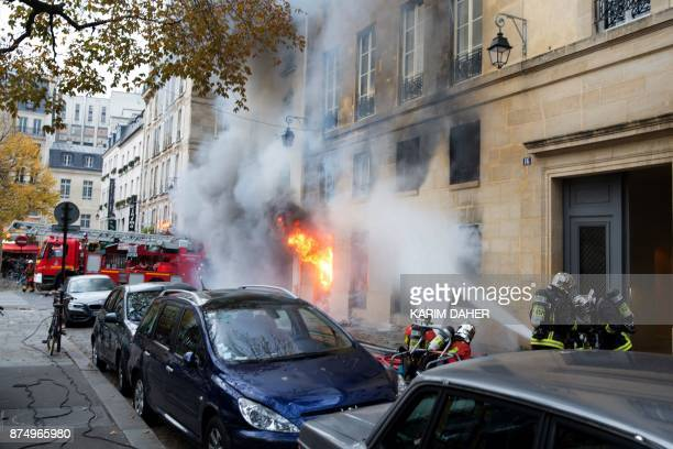 Firefighters work to put out a fire in 'La Hune' book shop in the SaintGermaindesPres district Paris on November 16 2017 Seven people were lightly...