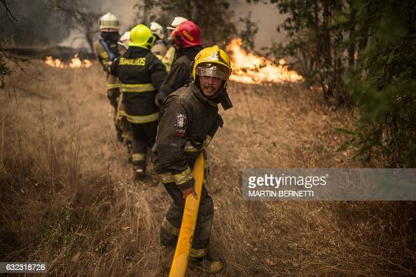 TOPSHOT Firefighters work to put out a fire in Pumanque 140 km south of Santiago on January 21 2017 The Chilean government declared a state of...