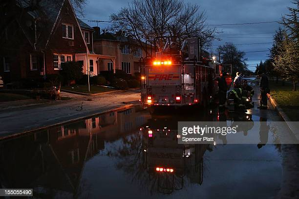 Firefighters work to put out remaining fires in the heavily damaged Rockaway section due to Hurricane Sandy on October 31 2012 in the Queens borough...