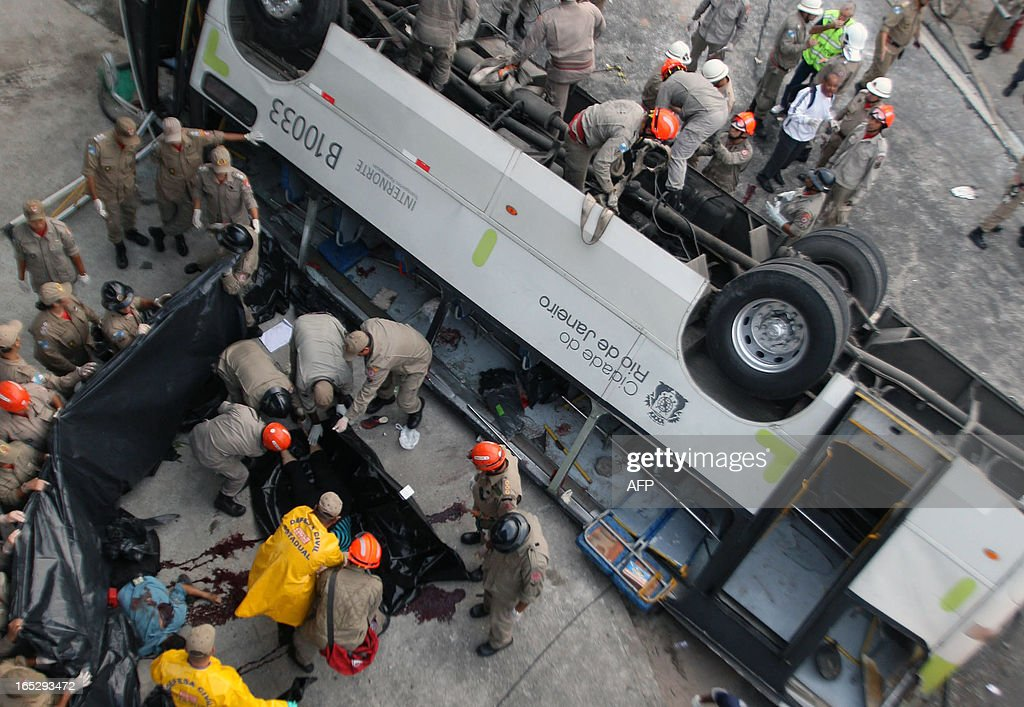 Firefighters work with a corpse after a bus fell from a bridge with a height of 15 meters in Rio de Janeiro, Brazil on April 2, 2013. The accident left 7 people dead and 11 injured.