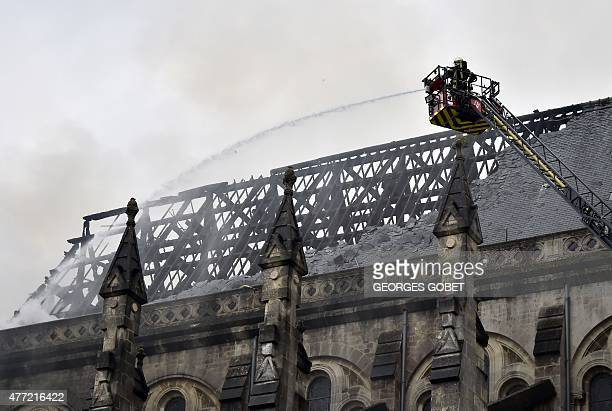 Firefighters works after a spectacular blaze that ravaged the roof of a 19th century basilica in Nantes western France on june 15 2015 The fire in...