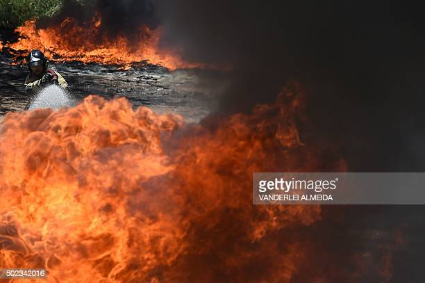 TOPSHOT Firefightes work on a fire in a LIGHT energy company plastic ducts storage at the entrance of the Ilha do Governador neighborhood in Rio de...