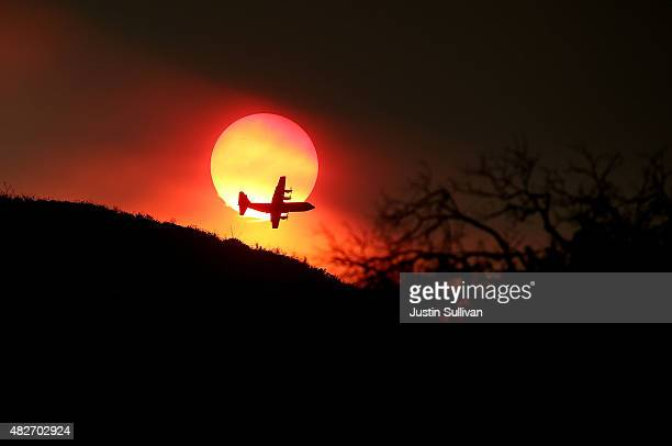 A firefighting air tanker flies in front of the setting sun while battling the Rocky Fire on August 1 2015 near Clearlake California Over 1900...