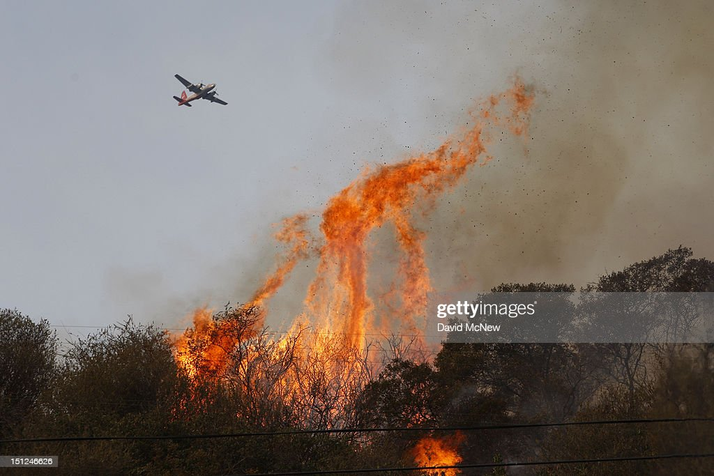 A firefighting air tanker flies over flames at the Williams fire in the Angeles National Forest on September 4, 2012 north of Glendora, California. The fire began late September 2, putting an early end to Labor Day weekend camping and hiking for vacationers, who were evacuated from the area as it spread to more than 4,000 acres in size. Officials project that it will take at least another week to establish a containment line around the fire which is burning in rugged and difficult to reach backcountry.