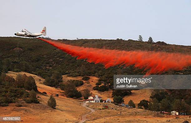 A firefighting airplane drops fire retardant on a house while battling the Rocky Fire on July 31 2015 in Lower Lake California Over 900 firefighters...