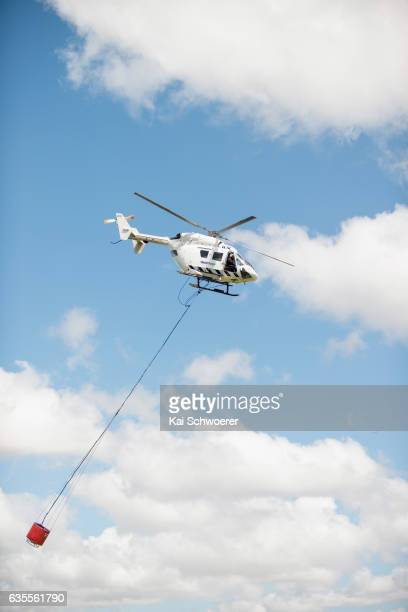 A firefighting helicopter carries water to extinguish fires on February 16 2017 in Christchurch New Zealand A state of emergency has been declared in...