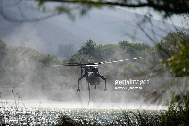 A firefighting helicopter dips into Lake Hughes as it continues to battle the Powerhouse wildfire on June 3 2013 in Palmdale California Nearly 2200...