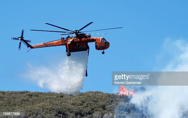 A firefighting helicopter drops a water on a burning hillside in Lake Hughes on June 3 2013 in Palmdale California Nearly 2200 firefighters have been...