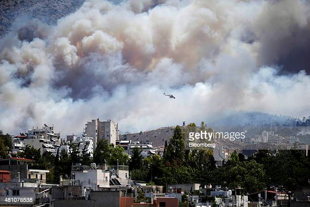 A firefighting helicopter drops water on a forest fire near the eastern residential suburbs of Athens Greece on Friday July 17 2015 Germany's...