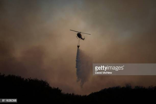 A firefighting helicopter drops water on the Whittier Fire on July 9 2017 near Santa Barbara California The Whittier Fire and the Alamo Fire together...