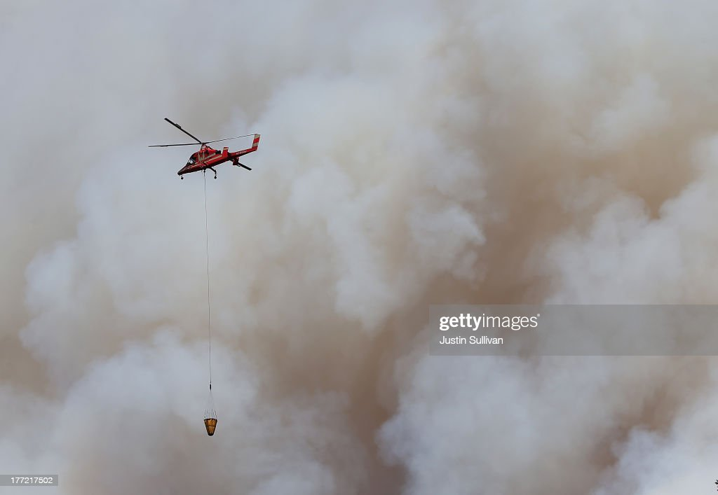 A firefighting helicopter flies in front of a plume of smoke from the Rim Fire on August 22, 2013 in Groveland, California. The Rim Fire continues to burn out of control and threatens 2,500 homes outside of Yosemite National Park. Over 1,000 firefighters are battling the blaze that was reduced to only 2 percent containment after it nearly tripled in size overnight.