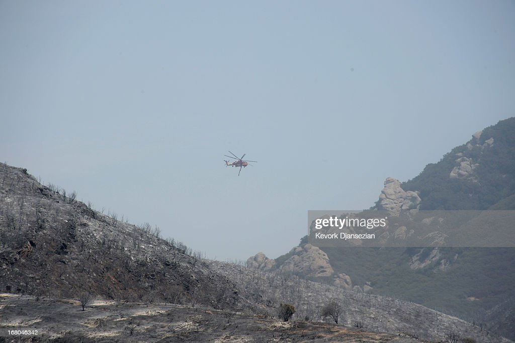 A firefighting helicopter flies over the scortched landscape of Pt. Mugu State Park on May 4, 2013 in Newbury Park, California. Nearly 1,000 firefighters continue to battle wind and dry conditions with over 28,000 acres burned and only 20% containment.