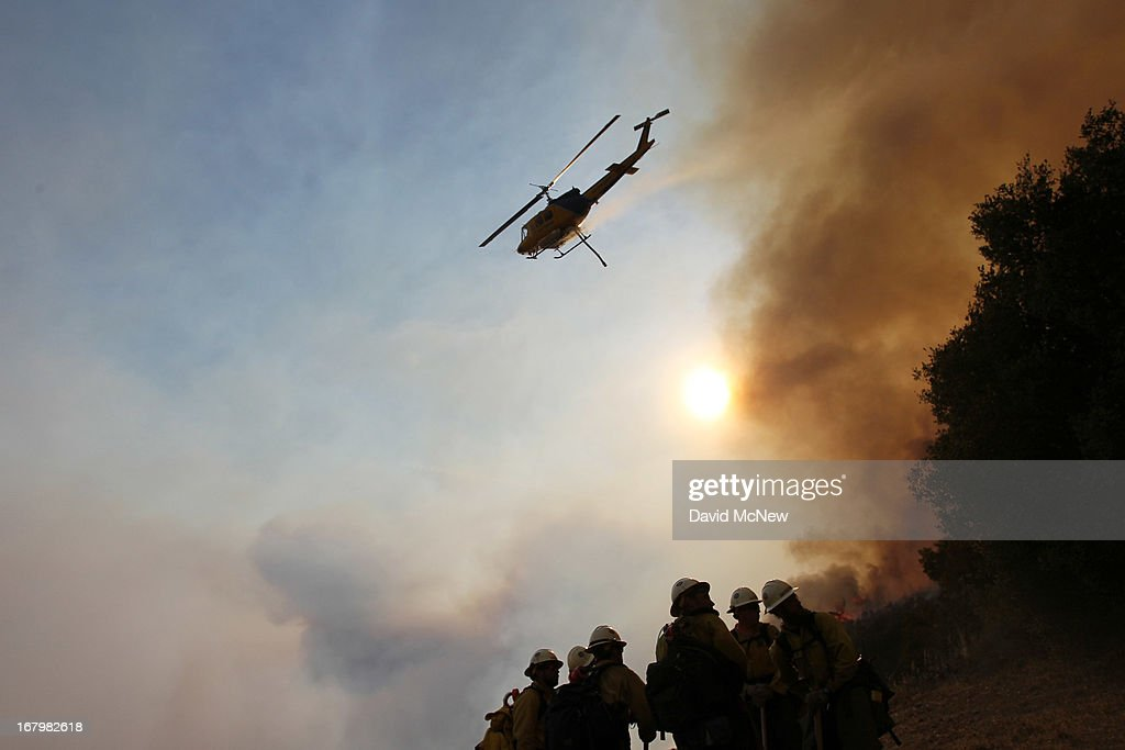 A firefighting helicopter makes a water drop above the Type 1 Interagency Hotshot Crew (IHC), based out of the Lone Peak Conservation Center, in Draper, Utah as the Springs fire continues to grow on May 3, 2013 near Camarillo, California. The wildfire has spread to more than 18,000 acres on day two and is 20 percent contained.