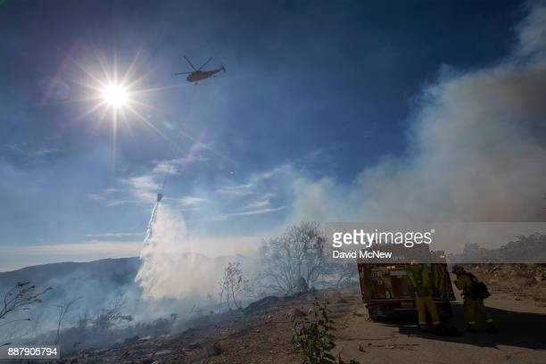 A firefighting helicopter makes a water drop at the Thomas Fire on December 7 2017 near Fillmore California Strong Santa Ana winds are pushing...