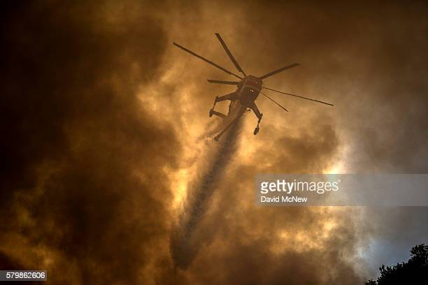 A firefighting helicopter makes a water drop near homes at the Sand Fire on July 24 2016 in Santa Clarita California Tripledigit temperatures and dry...