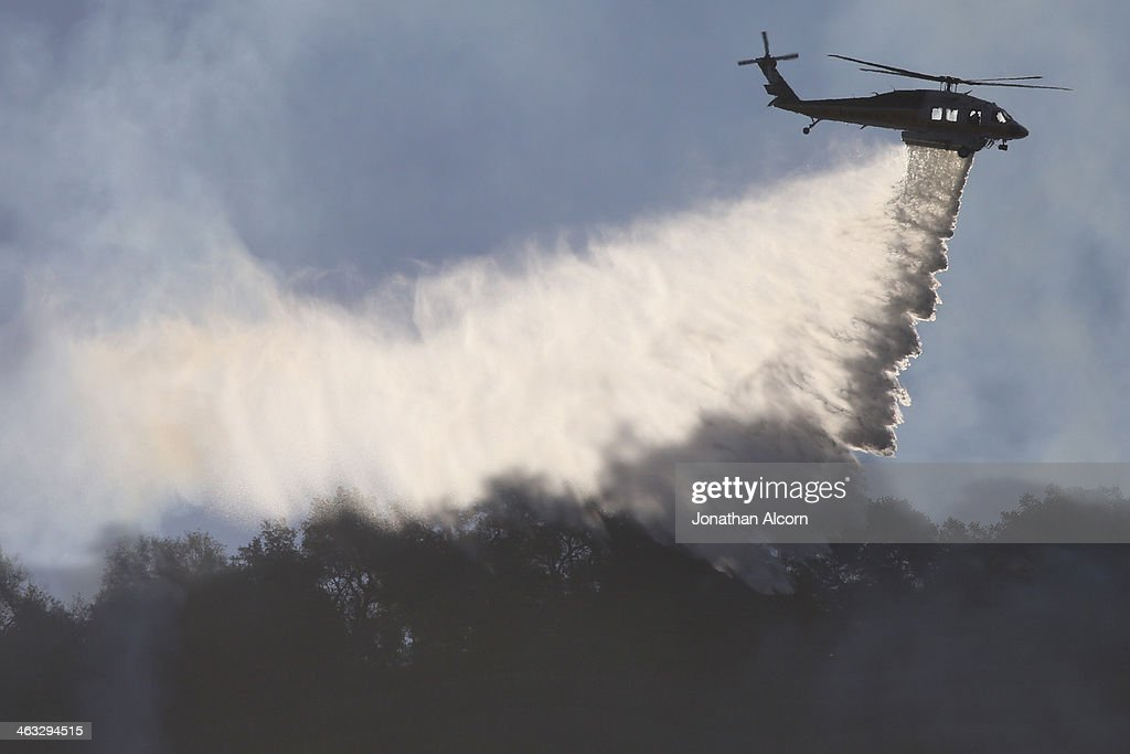 A firefighting helicopter makes a water drop on the Colby Fire burning for a second day in the hillside above Highway 39 on January 17, 2014 in Azusa, California. The so-called Colby Fire, has burned about 1,700 acres in the Angeles National Forest north of Glendora and Azusa.