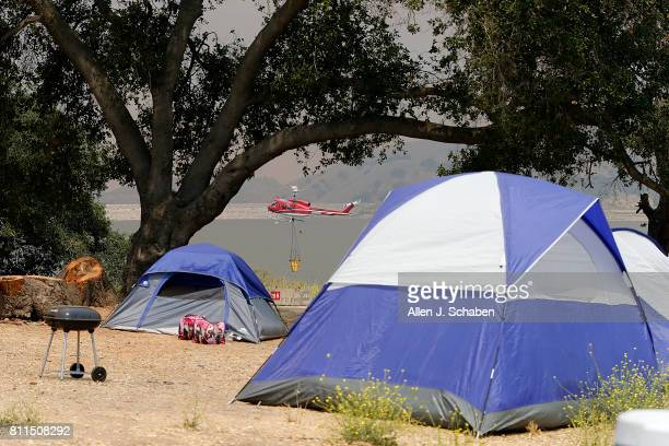 A firefighting helicopter prepares to draw water from the lake as tents food and personal belongs remain abandoned after campers were evacuated from...