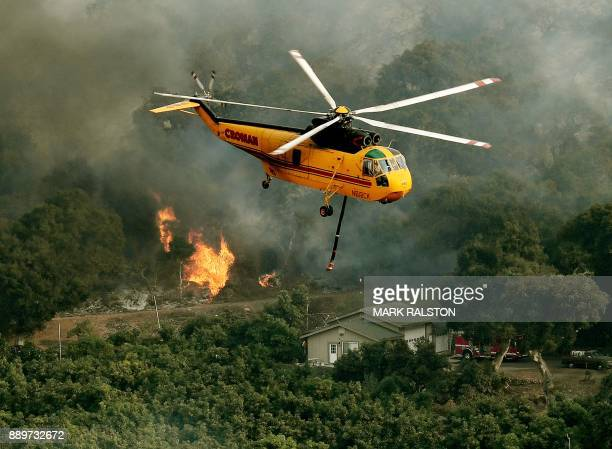 Firefighting helicopters try to save a house from the Thomas wildfire in Carpinteria California on December 10 2017 The Thomas fire is only 15...