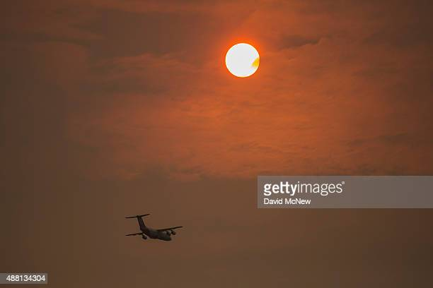 A firefighting jet flies before a smoky sunset at the Butte Fire on September 13 2015 near San Andreas California California governor Jerry Brown has...