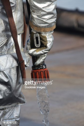 Firefighting Marine tests his hand line nozzle to check the water flow.