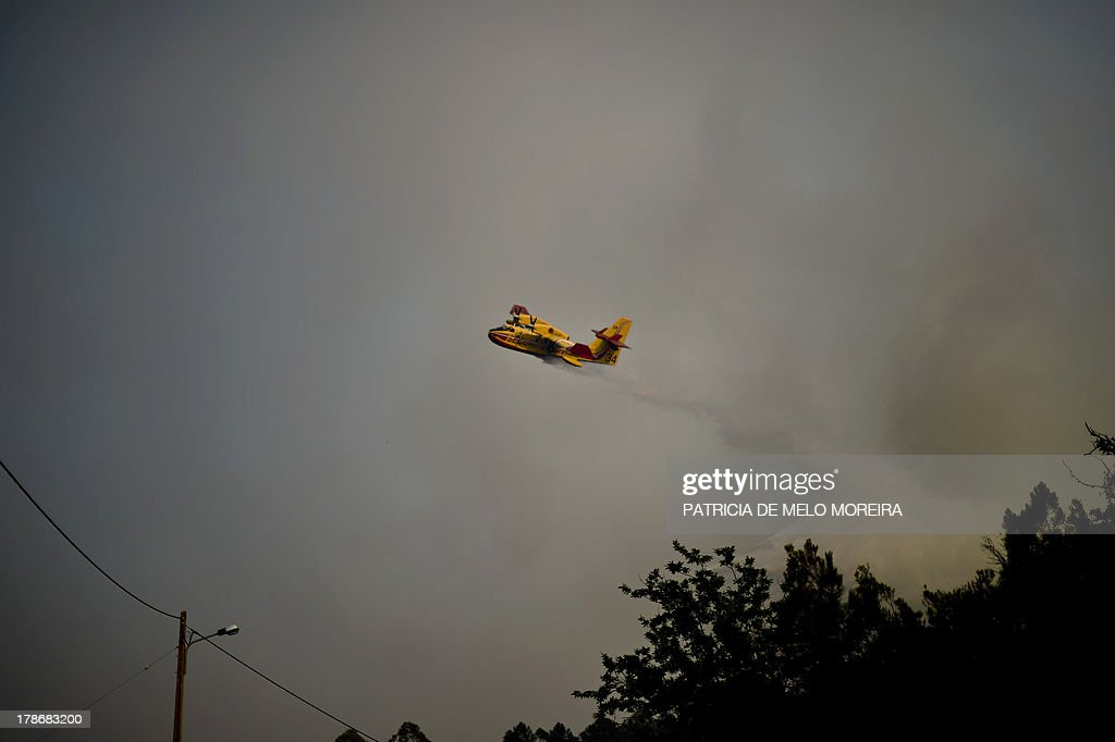 A fire-fighting plane helps extinguishing a fire in the Caramulo mountain, central Portugal, on August 30, 2013. Firefighters battled wildfires on August 30 in Portugal where they have claimed five lives and tamed another major blaze in northern Spain, officials said. In Portugal, some 1,400 firefighters backed by Spanish and French aircraft were battling a series of fires that have ravaged thousands of hectares of forest in the north and centre of the country.